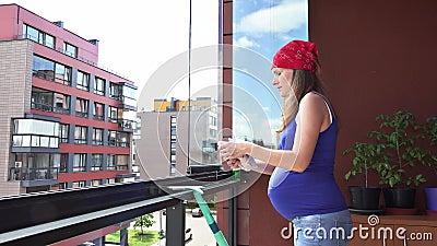Ventana de cristal de limpieza feliz de la mujer embarazada con la logia del paño del trapo en casa metrajes