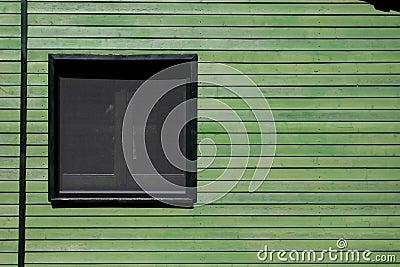 Ventana en pared de madera verde