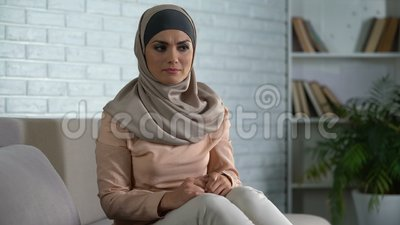 Verärgerte arabische Frau sitzt auf dem Sofa zu Hause, fühlt sich verletzt und enttäuscht, Krise stock video footage
