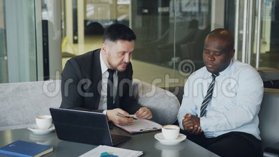 Verärgerter Geschäftsmann im schwarzen Anzug kritisiert streng seinen Afroamerikanerangestellten während der Sitzung im modernen  stock video