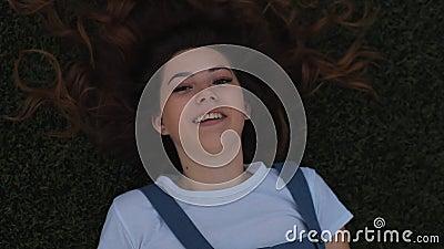 Ver a partir de cima Linda jovem mulher deitada no campo na grama verde e rindo Ao ar livre Aproveite a Natureza Saudável vídeos de arquivo