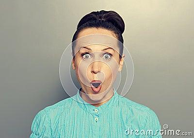 Verbaasde jonge vrouw in blauw overhemd