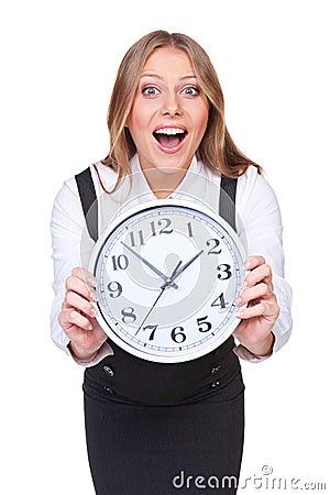 Verbaasde jonge vrouw die de klok toont