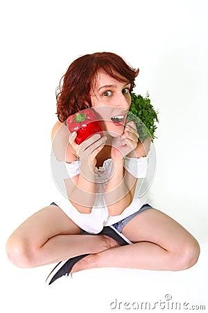 Verbaasde jonge vrouw met groenten