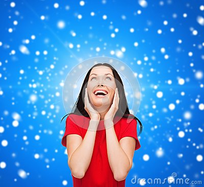 Verbaasde lachende jonge vrouw in rode kleding