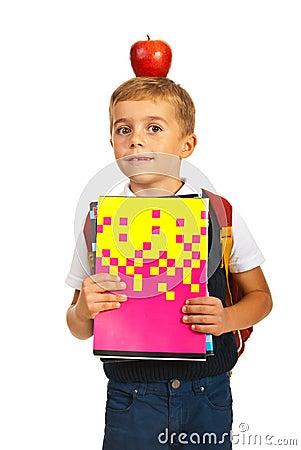 Verbaasde schooljongen met appel op hoofd