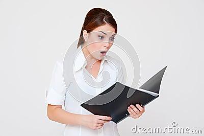 Verbaasde vrouw die in haar rapport kijkt