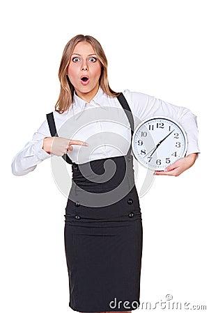 Verbaasde vrouw die op de klok richt