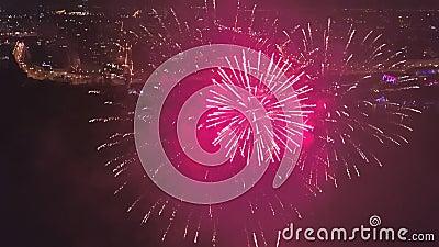 Verbazende mooie roze en groene klappen die van vuurwerk, over het panorama van de nachtstad vliegen stock videobeelden
