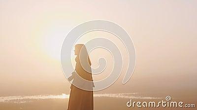 Verbazingwekkende abstracte achtergrondfoto van een gelukkige vrouw met een camera die langs een verbluffende roze zonneschijn lo stock footage