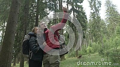 Verbonden door technologie jong paar van wandelaars die smartphone voor videovraag in bos gebruiken die de reiservaring delen stock video