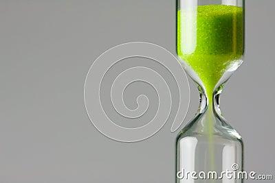 Verde de disminución. Arena verde del vidrio de la hora