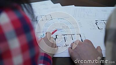 Vergadering van twee architectuur in bureau om plan van gebouwen te bespreken Geen gezicht stock videobeelden