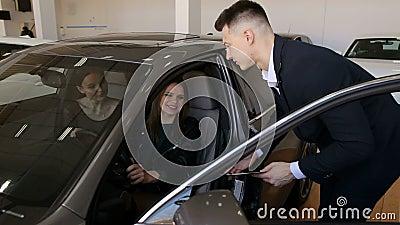 Verkaufsberater zeigt zu junge Mädchen ein zu kaufen Neuwagen, stock video