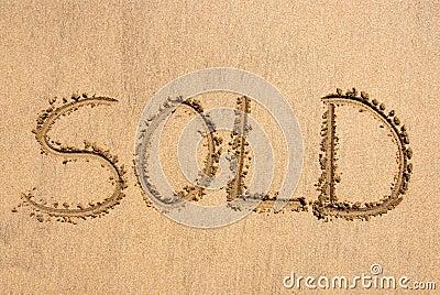?Verkocht? geschreven op zand
