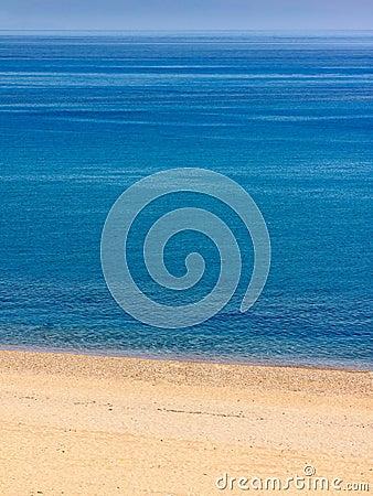 Verlaten strand met briljante blauwe overzees