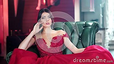 Verleidelijk Spaans jong meisje in zitting van de glamour de rode avondjurk op uitstekend leunstoel middelgroot schot stock video