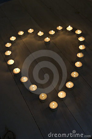 Verlichte kaarsen die in een vorm van het hart worden geplaatst