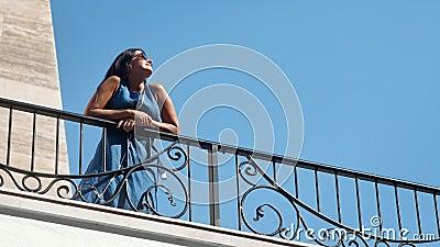 Verminderde elegantie-gelooide vrouw in jurk die geniet van zonneschijn die op balkon staat stock footage