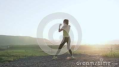 Verpacken ` s Mädchen, das Training auf Berg bei Sonnenuntergang oder Sonnenaufgang tritt sie tun, das Trainieren hoch herein die stock video