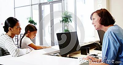 Verpleegster die met een patiënt bij teller spreken stock video