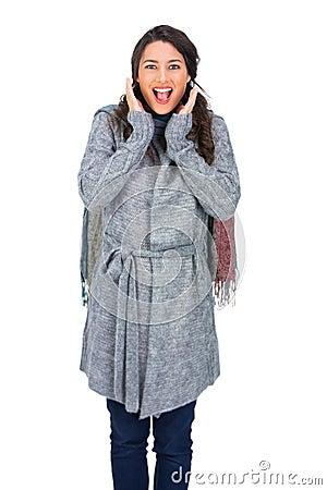 Verrast brunette die de winterkleren het stellen dragen
