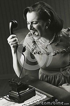 Verärgerte Frau, die am Retro Telefon schreit