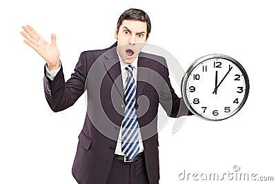 Verärgerter Mann in einer Klage, die eine Uhr und ein Gestikulieren hält