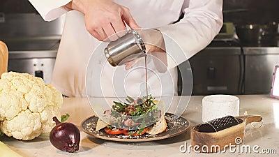 Versamento o salsa di chef sopra l'insalata prima di servirla al cliente stock footage