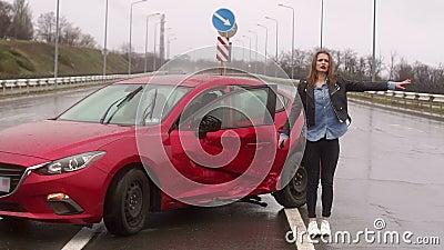 Verschrikkelijk meisje huilend op de weg na een zwaar auto-ongeluk in de regen stock video