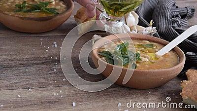 Verter aceite de oliva en sopa tradicional de frijoles calientes con pan de maíz, ajo y aceite de oliva Plato vegetal sano metrajes