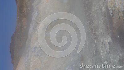 Vertical shot natural aggressive volcanic landscape - hot spring water stream surrounded by fumaroles. Geothermal field stock video footage