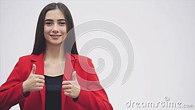 Verticale d'un beau jeune brunette Regardez dans l'appareil-photo Pendant le ceci elle a soulevé ses bras, montrant un geste banque de vidéos