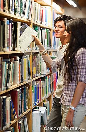 Verticale de jeunes étudiants choisissant un livre