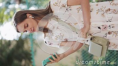 Vertikales Video Hübsch kaukasisch-braunes Haarbürmchen mit weißblütenweißem Kleid mit Tag Cross ihre Schulder mit Holding stock footage