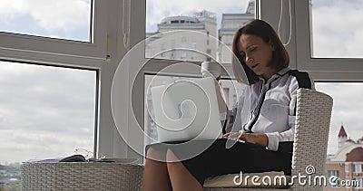 Vertrouwd, stijlvol en succesvol zakenvrouw met kop koffie en kijkend naar een monitor op een moderne werkplek met grote vensters stock video
