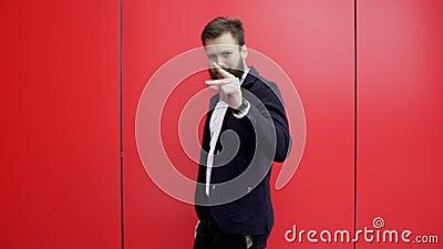 Vertrouwde man knipt zijn vingers en wijst met een wijsvinger in de camera terwijl hij langs de camera loopt. stock videobeelden