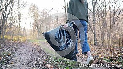 Vervuiling van natuur en milieu Vrouwelijke benen, een grote zwarte vuilniszak Het begrip kunstmatige verontreiniging van stock footage