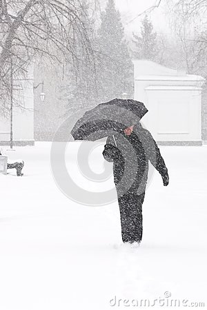 Free Very Bad Weather In A City In Winter: Heavy Snowfall And Blizzard. Male Pedestrian Hiding From The Snow Under Umbrella, Vertical Royalty Free Stock Images - 107863669