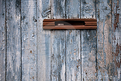 Very old postbox in wheathered wooden fence