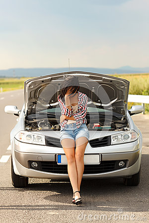 Very sad woman in front of broken car
