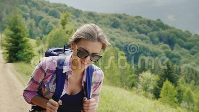 A very tired woman tourist with a backpack goes up the mountain path. Willpower and physical endurance. Slow motion video stock footage
