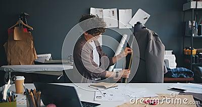 Vestuário de medição da costureira bonita no manequim que redige a informação no caderno video estoque