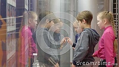 Vetrina di vetro sembrare dell'adolescente del gruppo sulla mostra in museo storico archivi video
