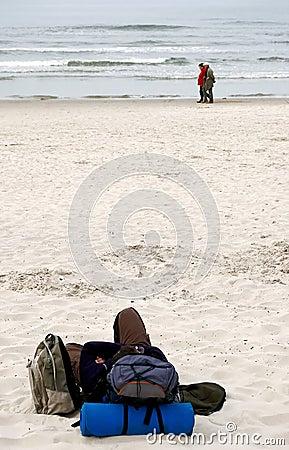 Viaggiatore con zaino e sacco a pelo alla spiaggia.