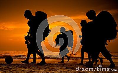Viaggiatori con zaino e sacco a pelo sulla spiaggia