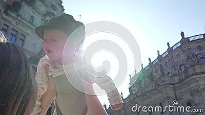 Viajando com crianças, a mãe joga com o filho novo na rua no luminoso no fundo do céu filme