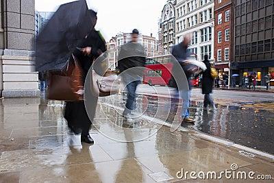 Viajantes de bilhete mensal ocupados de Londres na chuva de derramamento