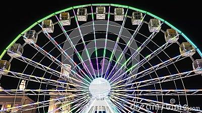 Viaje en rueda de ferris iluminado girando por la noche en un carnaval, parque de atracciones, parque temático, feria, parque de  almacen de metraje de vídeo