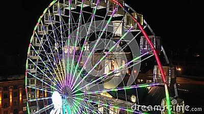 Viaje en rueda de ferris iluminado girando por la noche en un carnaval, parque de atracciones, parque temático, feria, parque de  metrajes